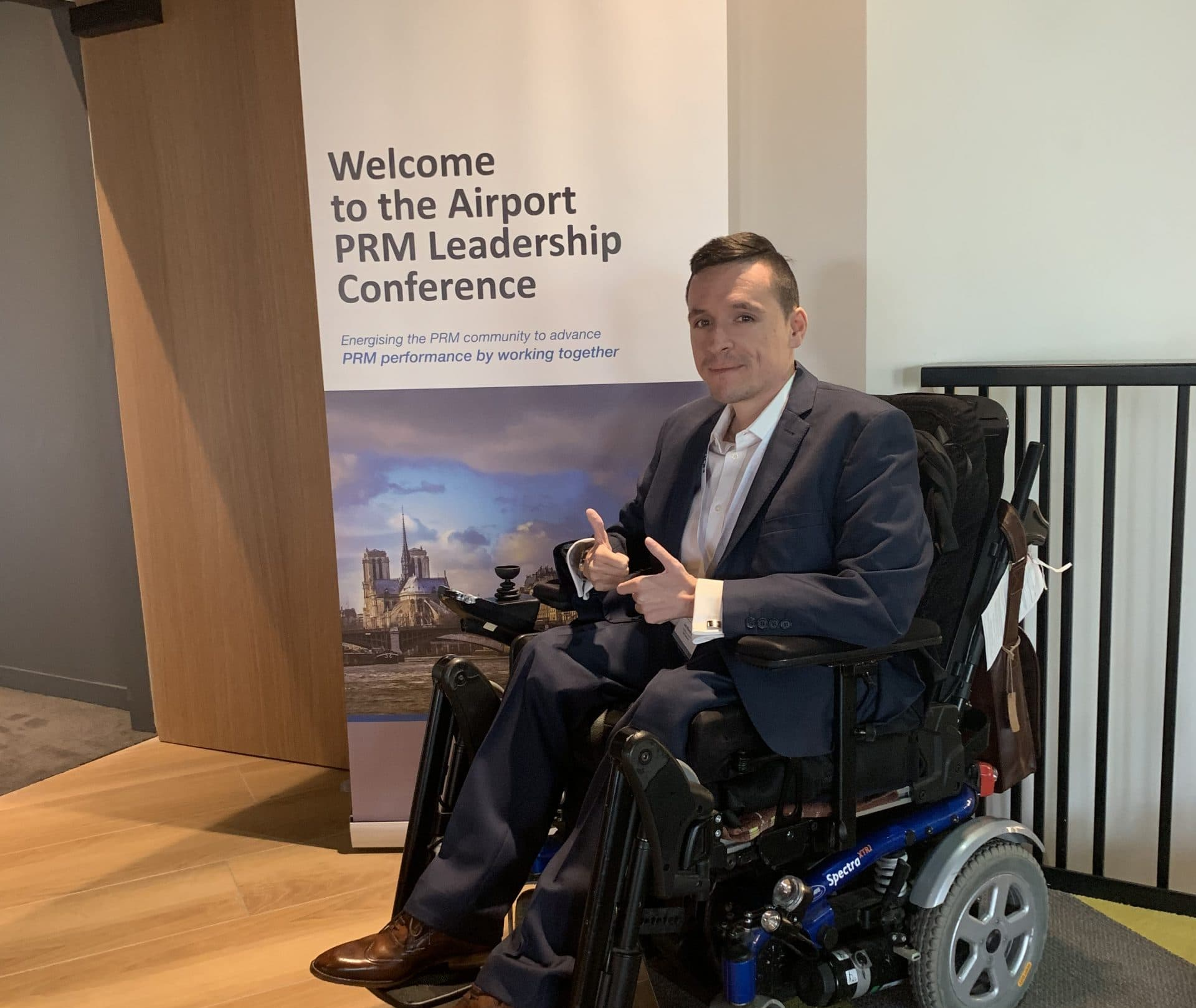 Josh in his wheelchair with his thumbs ups. Behind in him is a poster which says 'welcome to the airport PRM leadership conference