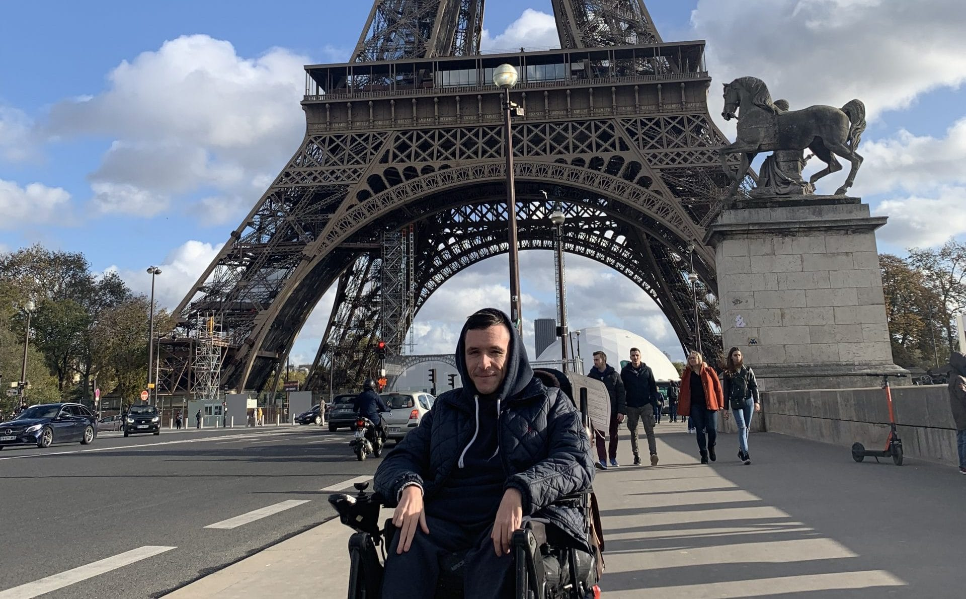 Josh is sat in his wheelchair with the Effiel tower in the background and a statue of a horse to his right.