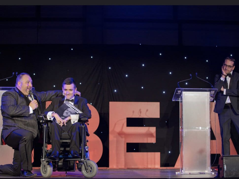 Josh is on stage receiving his award, being interviewed by Wynn Evans. Josh is holding a trophy with GBEA letters on the stage in the background