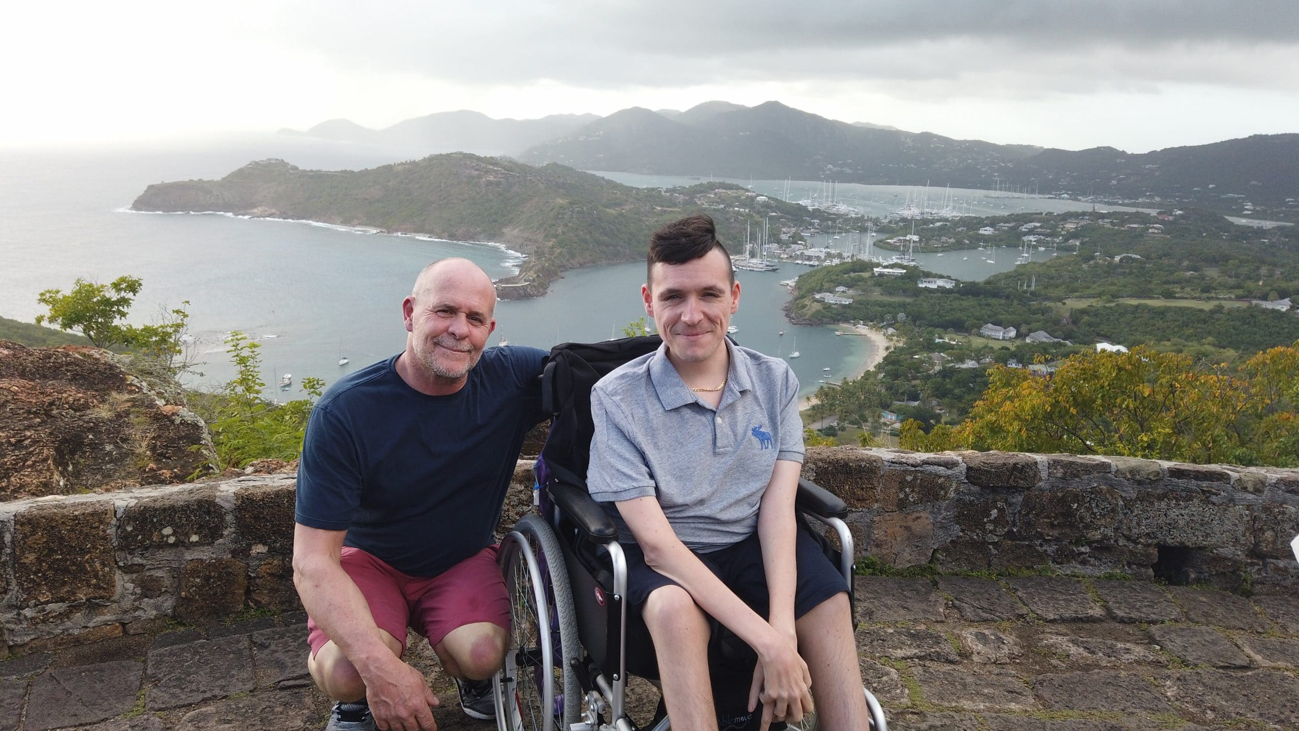 Josh is sat in his manual wheelchair with his fathers arms around him crouched. In the background is the sea, boats, rain in the hills.
