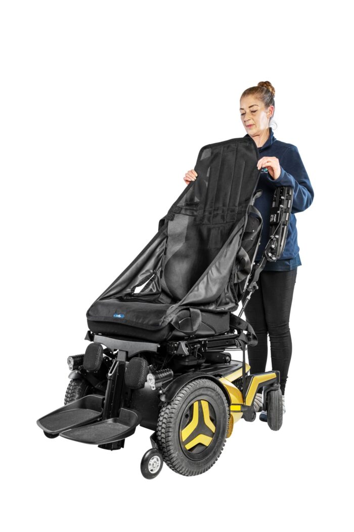 An assistant has placed a transferring sling into a wheelchair for a wheelchair user. They are holding it up from behind the wheelchair by the head rest