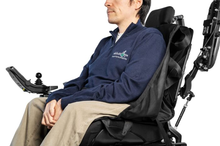 A wheelchair user is sat in a powered wheelchair onto of an ablesling which blends discreetly in with the wheelchair