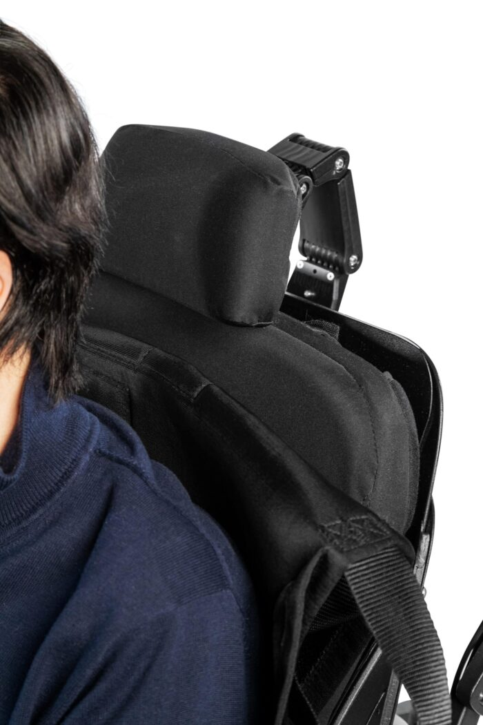 A wheelchair user is sat in his wheelchair with the ableSling headrest folded down behind his back so it is hidden when not in use.